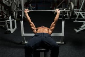Man lying on bench press lifting weights